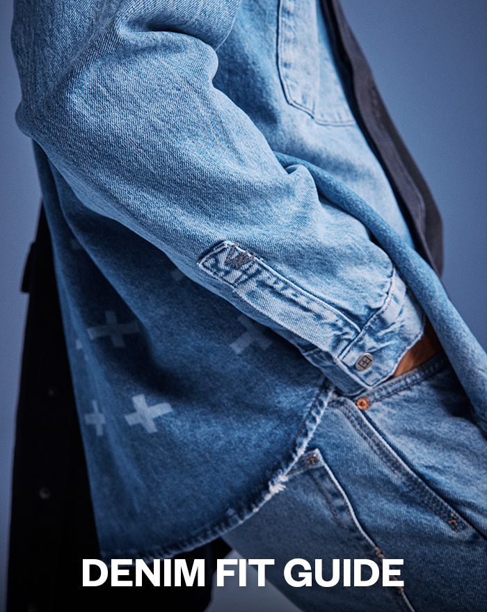 Mens denim fit guide featuring a blue denim shirt with white crosses on the back and a distressed edge. Styled with relaxed blue denim jeans for a casual look.