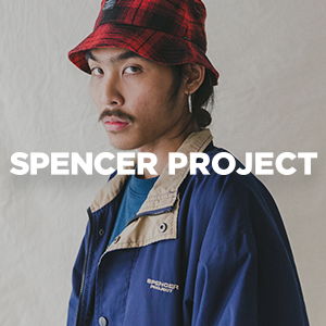 Male model wearing red and black check bucket hat with navy jacket looking at the camera with spencer project text over the top