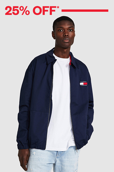 Male model wearing a navy Tommy Jeans jacket over a white tee and jeans on a grey background with 25% off red text