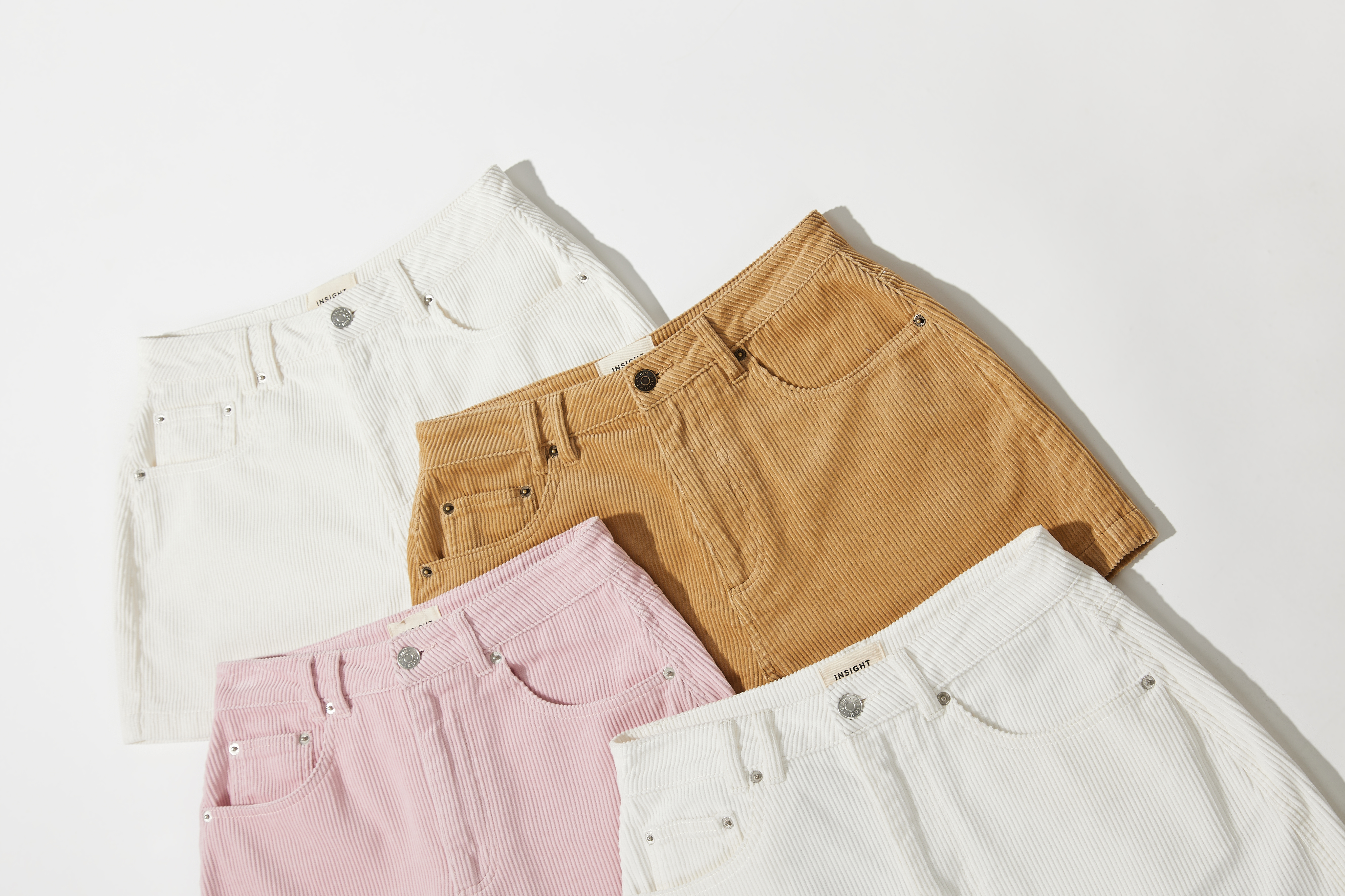 Four pairs of cord shorts flat laid on a white background