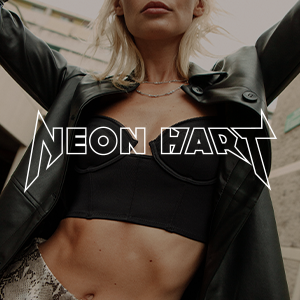 female model wearing black leather blazer and crop top with neon hart text over the top