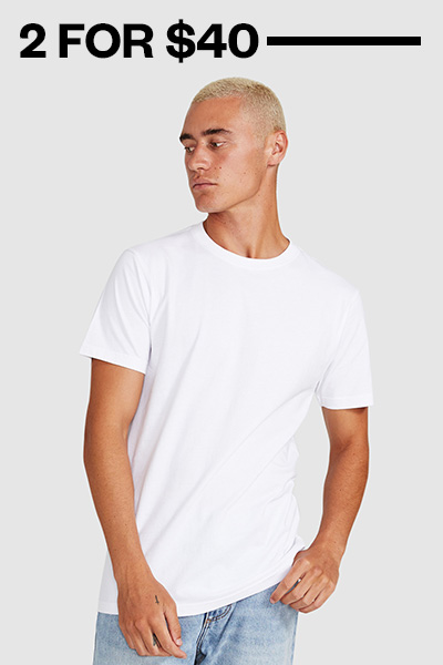 A mens basic white crew neck t-shirt with rolled up sleeves. Styled with tousled hair and sideburns under the cheekbone.