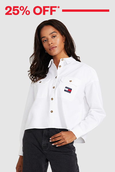 Female model wearing white Tommy Jeans jacket and black jeans on a grey background with 25% off red text.