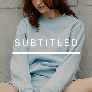 Female model wearing blue jumper and shorts with subtitled white text over the top