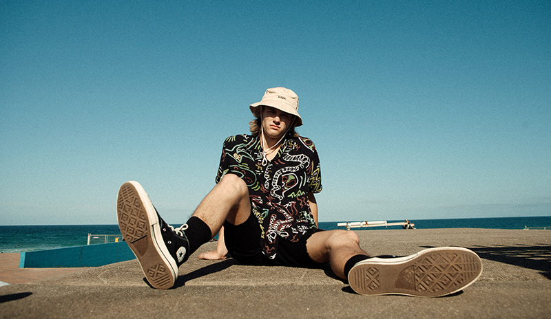 Model sitting down at beach pool wearing black shorts and printed shirt with sneakers and a bucket hat.